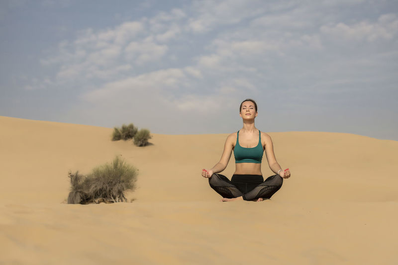 Woman exercising on sand against sky