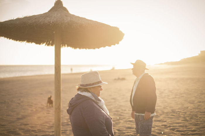 elderly senior couple on the beach with umbrela and hats Beach Beauty In Nature Bonding Day Friendship Lifestyles Love Men Nature Outdoors Real People Sand Sand Dune Scenics Sea Sky Standing Sunset Togetherness Two People Umbrela Vacations Women