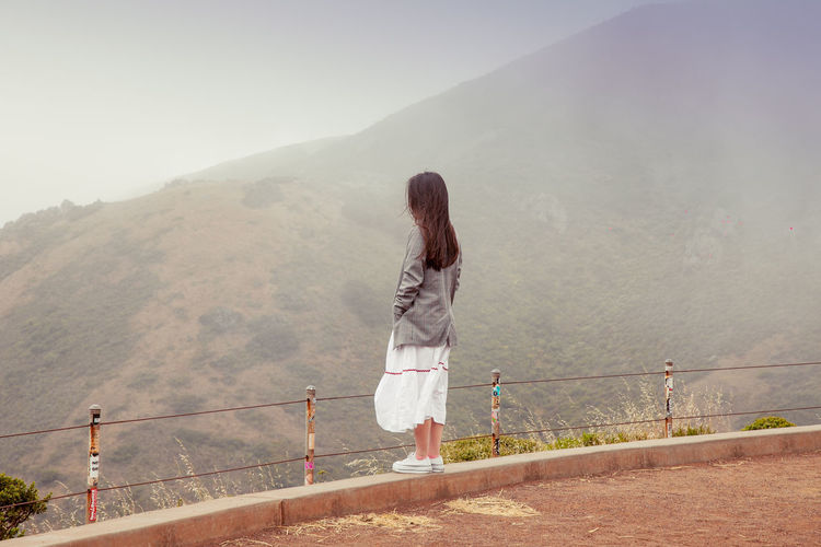 Stylish tourist girl admires wonderful landscape. woman admire mountains from observation desk.