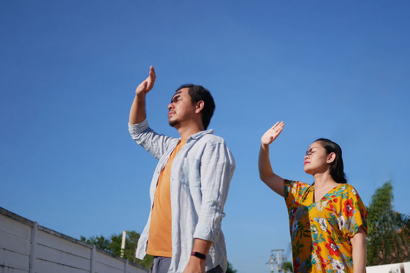 Low angle view of friends standing against clear blue sky