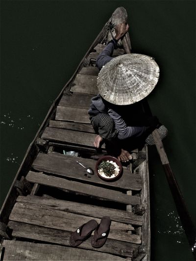 High Angle View Of Man Wearing Asian Style Conical Hat While Sitting On Wooden Boat Over River