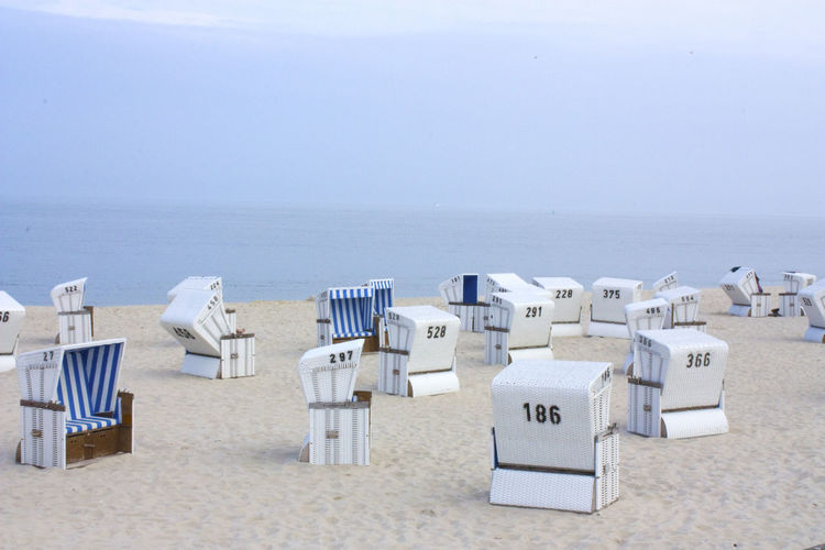 Tilt-shift image of hooded beach chairs with numbers on sand at beach against sky