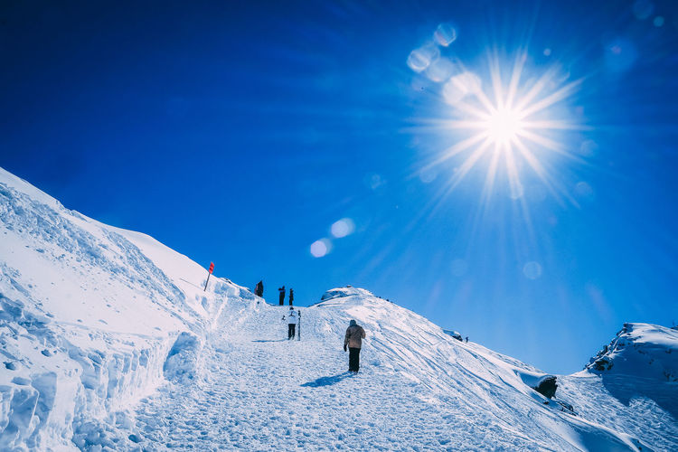 People skiing on snowcapped mountain against blue sky