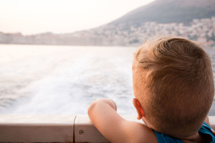 Small boy on cruising ship looking at the view from a deck and enjoying in summer day.