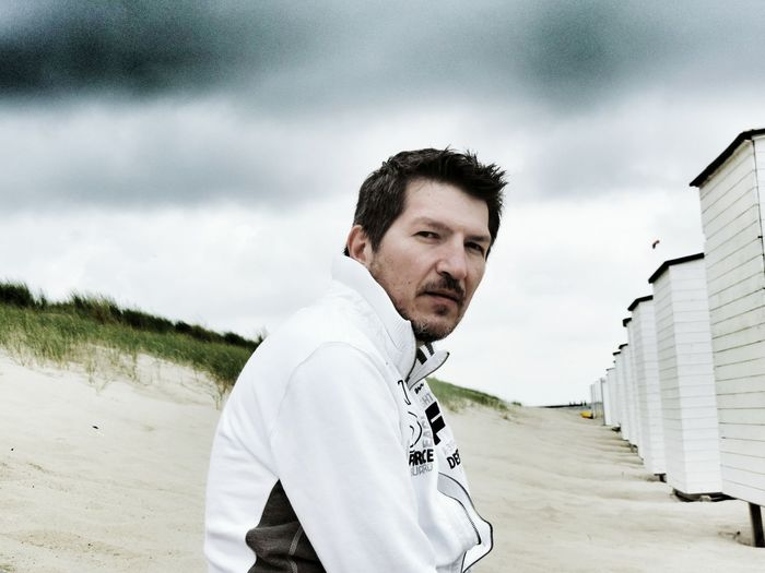 Portrait Of Serious Man On Beach By Huts Against Sky