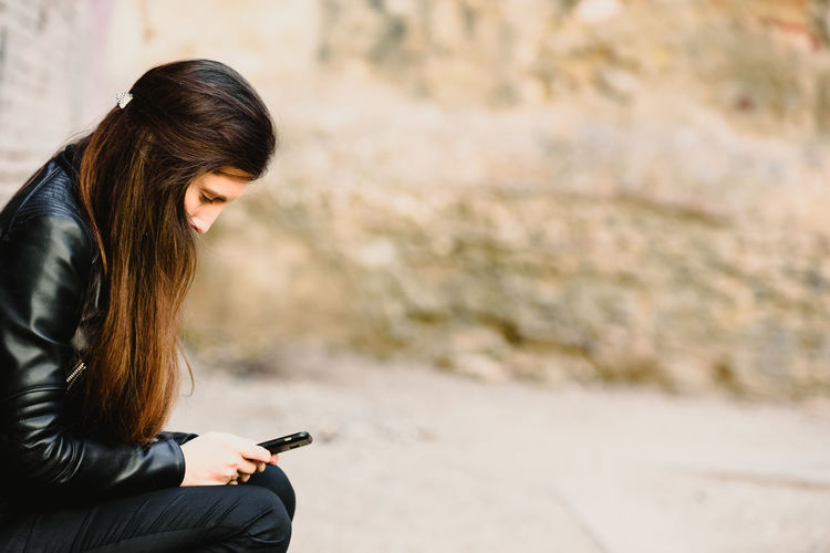 Side view of woman using mobile phone outdoors