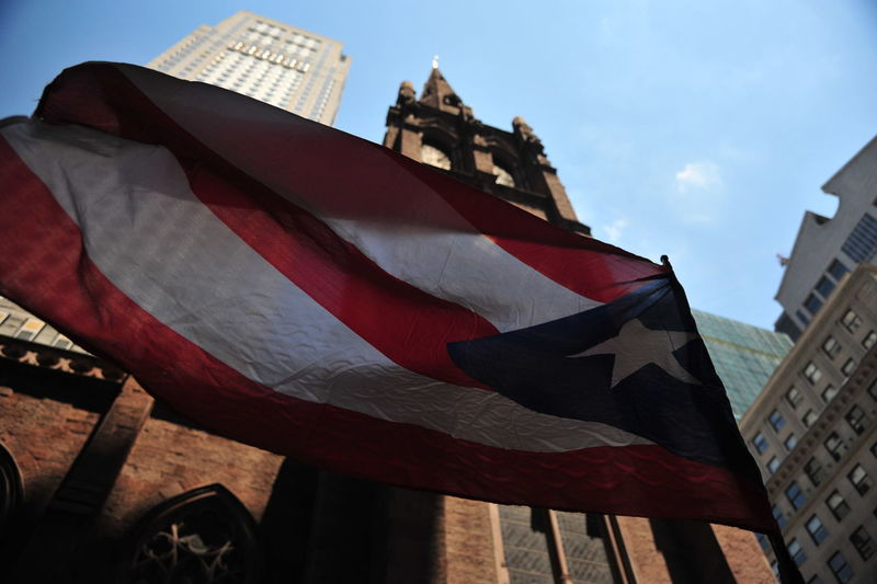 Low angle view of cuban flag waving against buildings and church