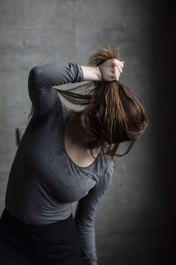 Young woman covering face with hair while standing against wall