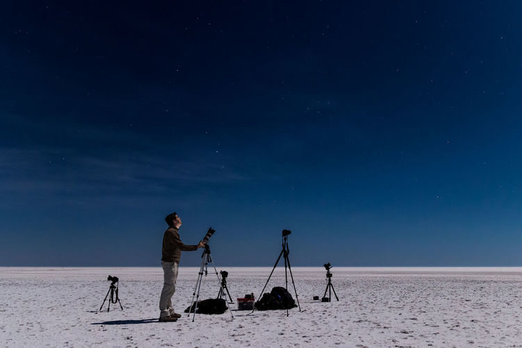 Man Taking Photos Of Starry Night