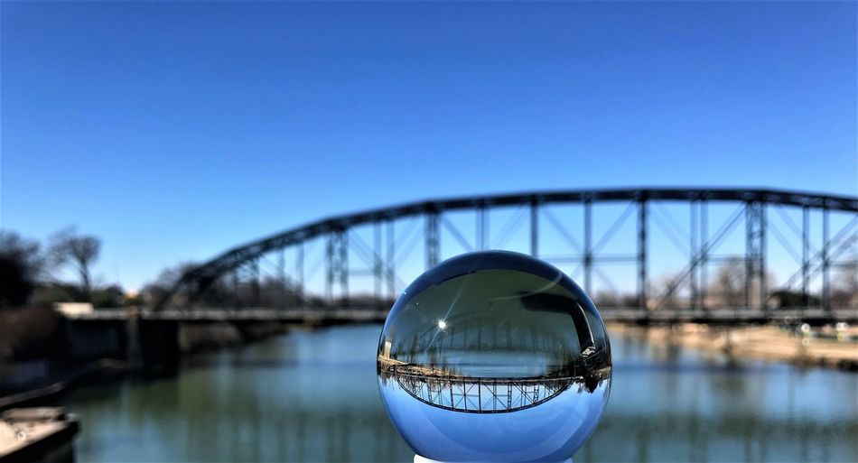 Reflection of arch bridge in crystal ball by river against clear blue sky