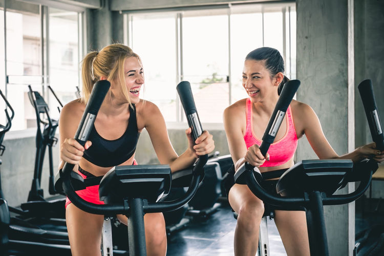 Happy young women on exercise bikes at gym