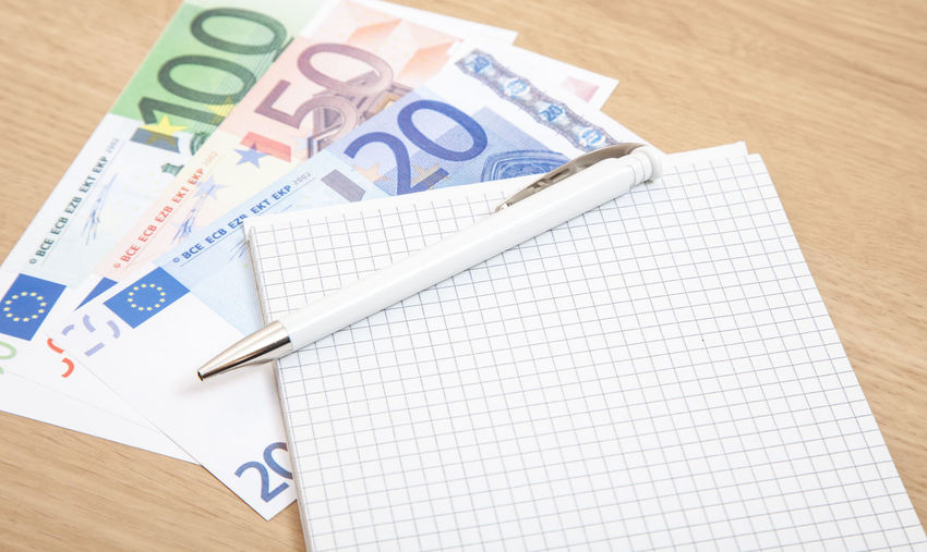 High Angle View Of Pen And Book Euro Banknotes On Table