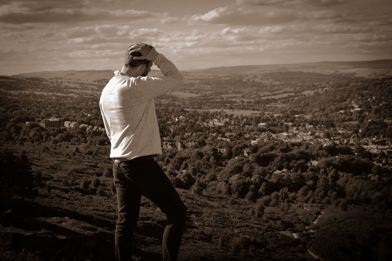 Rear view of man standing on mountain looking at landscape against sky