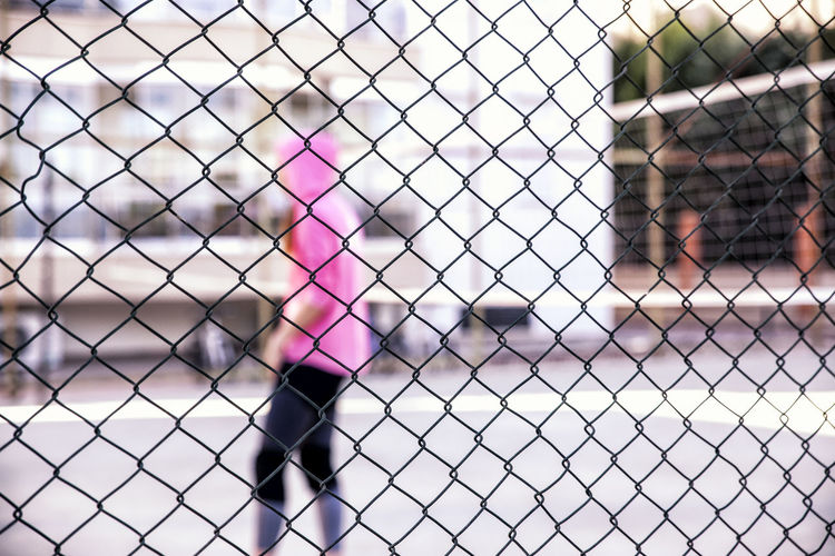 Woman standing on playing field seen through chainlink fence