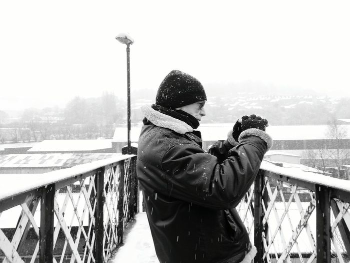 Mature man photographing while standing on footbridge during winter