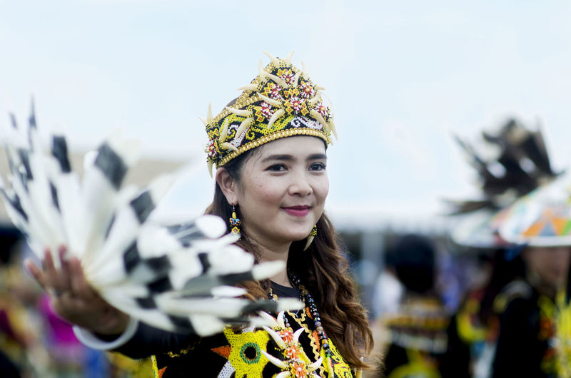 Smiling young woman wearing traditional clothing against sky