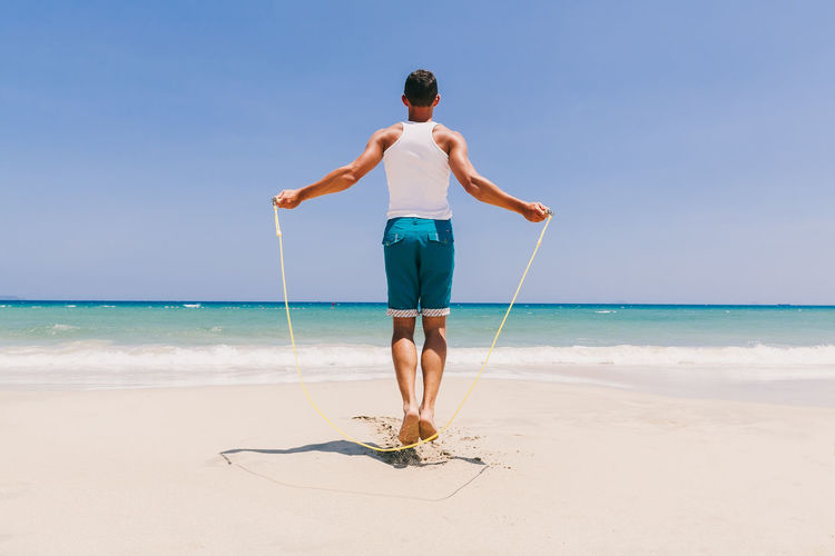 Full Length Of Man Exercising At Beach Against Clear Sky