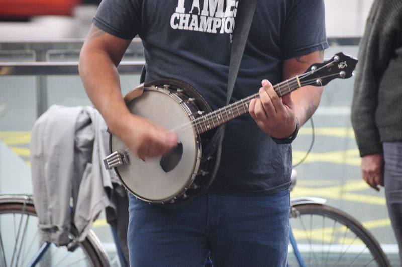Musical Instrument Music Midsection Arts Culture And Entertainment Holding Playing Men Performance String Instrument Musician Musical Equipment Guitar Front View Artist Casual Clothing One Person Real People Standing City Focus On Foreground Skill  Street Musician