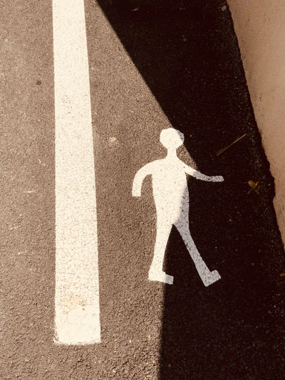 Asphalt Close-up Communication Day Direction Guidance High Angle View Human Representation Information Symbol Male Likeness Marking No People Outdoors Pedestrian Crossing Sign Representation Road Road Marking Sign Symbol Transportation White Color