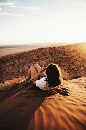 Woman Lying On Sand During Sunny Day