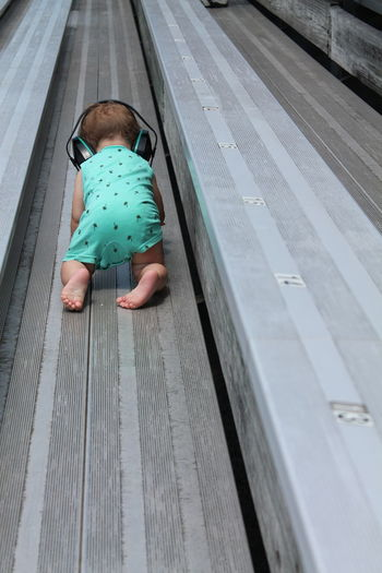 Baby Bleachers Blue Casual Clothing Crawling Day Headset Leisure Activity Lifestyles Part Of Racetrack Showcase June Unrecognizable Person