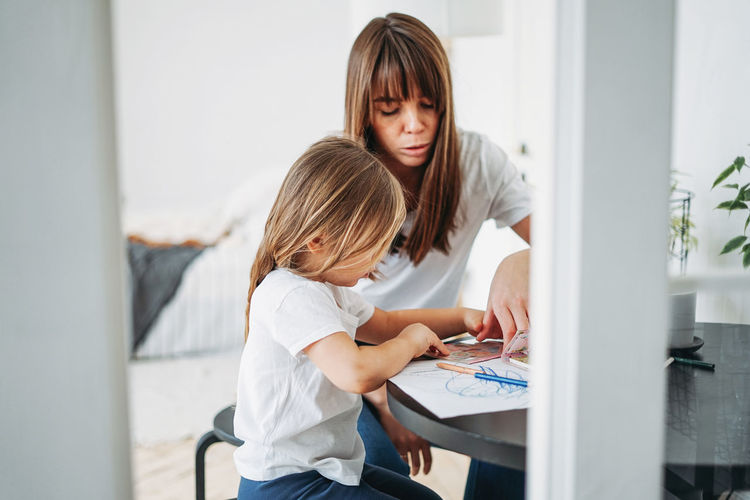 Mother assisting daughter drawing on paper