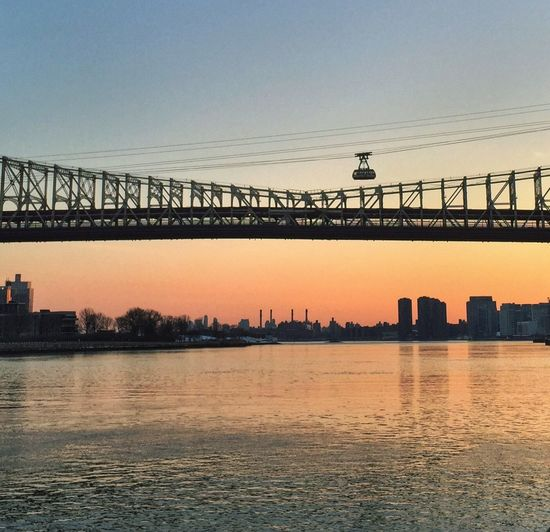 Low Angle View Of Bridge Over River In City Against Sky During Sunset