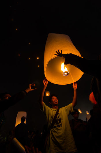 15 may 2014, Magelang, Indonesia : Participants releasing lanterns over the Borobudur temple in Magelang, Central Java during Vesak/Waisak Day celebrations. Arms Raised Burning Celebration Dark Glowing Group Of People Holding Human Arm Illuminated Lantern Leisure Activity Lifestyles Lighting Equipment Men Night Paper Lantern People Real People Traditional Festival