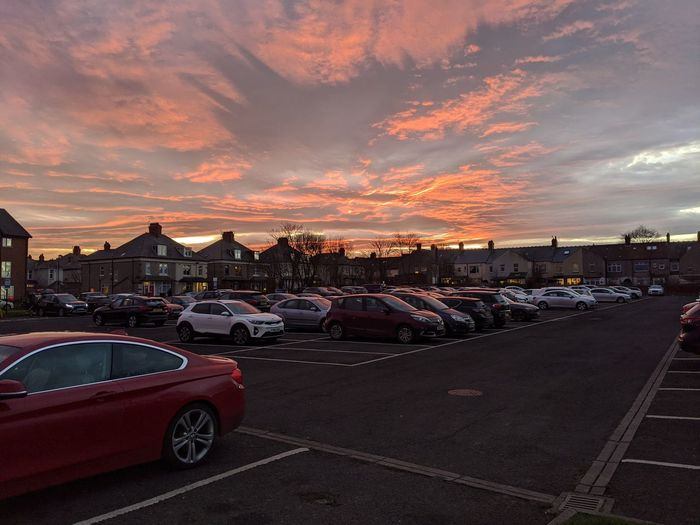 Cars on road in city against sky at sunset