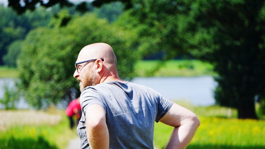 Rear view of bald man on field during sunny day