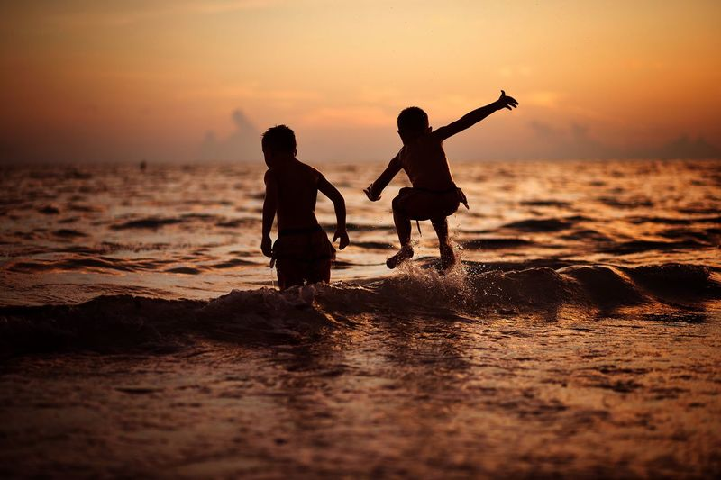 Two little boys jumping in ocean waves at sunset. EmNewHere Water Sunset Beach Sea Child Land Sky Childhood Playing Family Nature First Eyeem Photo