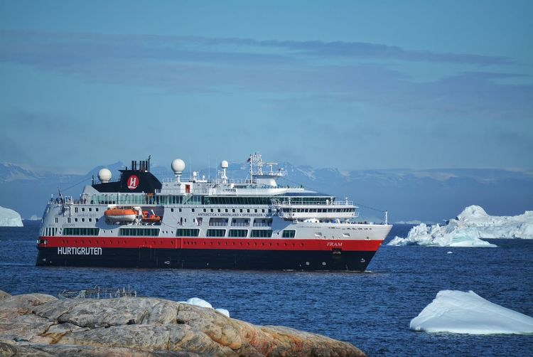 Ilulissat, Greenland, July | UNESCO world heritage site | impressions of Jakobshavn | Disko Bay Kangia Icefjord | huge icebergs in the blue sea on a sunny day | climate change - global warming | Hurtigruten ship anchored in the bay Greenland Travel Destinations UNESCO World Heritage Site Iceberg Icebergs Ice Sea White Nature No People Day Scenics - Nature Outdoors Water Climate Change Global Warming Melting Glacier Hurtigruten Nautical Vessel Mode Of Transportation Ship Cruise Ship Sailing Passenger Craft Cruise