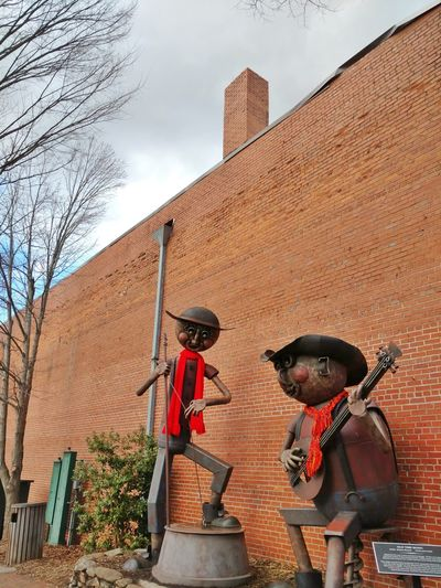 Adapted To The Citydowntown Waynesville Metal Musician!Downtown Waynesville, NC Metal Figures Architecture Building Exterior Red Brick Building Blue Sky Elevated Shot Red Brick Wall Band Figures EyeEm EyeEm Gallery Cell Phone Photography