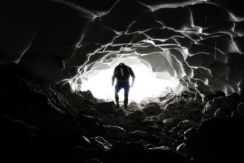 Rear view of silhouette person standing in cave