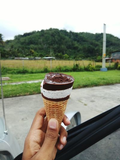 Close-up of hand holding ice cream cone on field