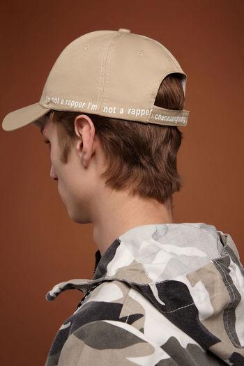 Portrait of boy wearing hat against gray background