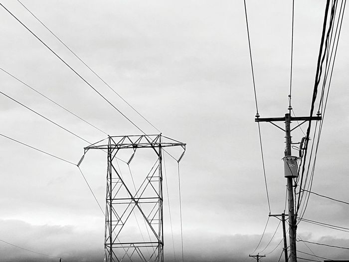 Low angle view of electricity pylons against cloudy sky