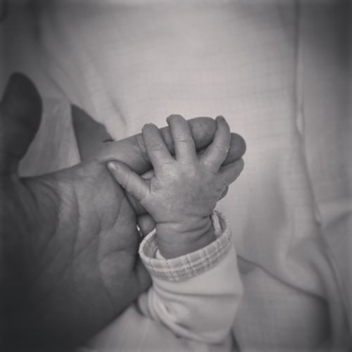 Cropped image of person holding baby hand sleeping on bed at home