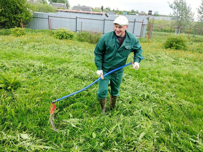 Smiling mature man raking grassy field by lake