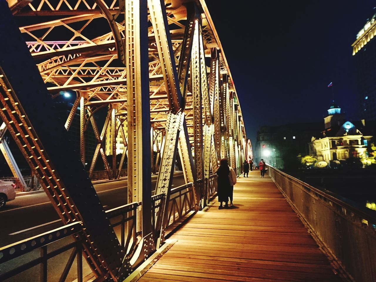 architecture, night, built structure, illuminated, bridge, bridge - man made structure, city, railing, real people, connection, the way forward, direction, building exterior, lifestyles, transportation, one person, men, incidental people, rear view, sky, outdoors, footbridge