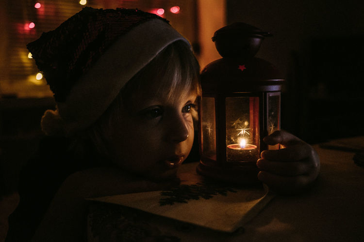 Portrait of child in santa's hat near candle in illuminated room at night