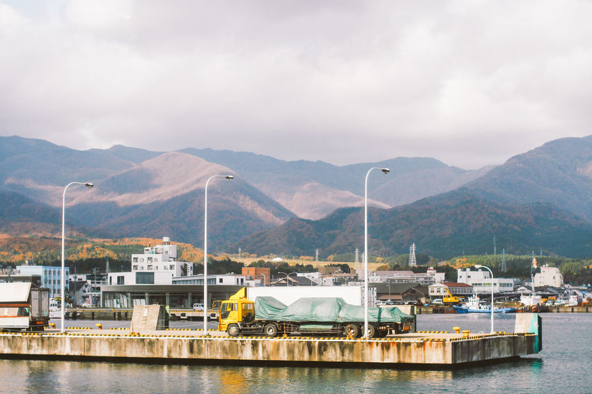 A yellow truck is waiting for goods in terminal Beach Building Good Hill Industrial Landscape Load Mountain Mountain Range Mountains Ocean Scenery Sea Ship Terminal Transportation Truck Waiting Water Market Bestsellers October 2016