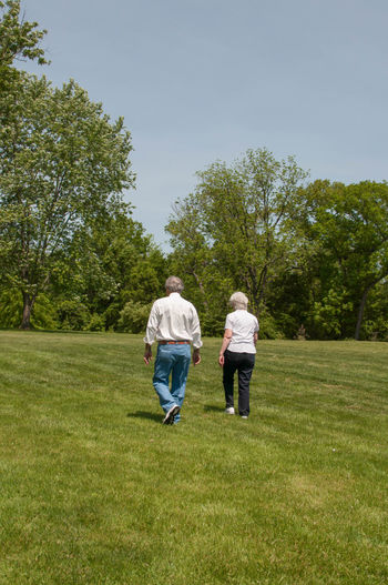Elderly Couple Walking Together Through a Field Husband Man Relationship Woman Adult Aged Bonding Elderly Full Length Leisure Activity Lifestyles Nature Older  Outdoors People Real People Rear View Senior Senior Man Senior Woman Togetherness Two People Walking Wife