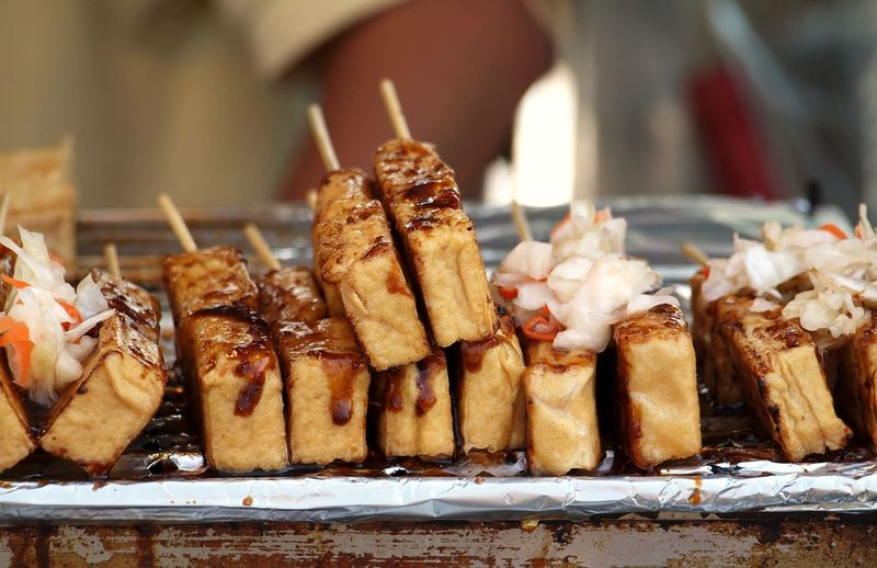 Deep fried stinky tofu or beancurd with chili sauce and pickled cabbage Bean Curd Chili Sauce Chinese Food Deep Fried  Fermented Pickles Skewered Food Smelly Stinky Tofu Street Food Worldwide Taiwan Food Tofu