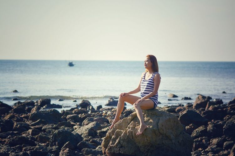 Sea Sky Beach Water Land Horizon One Person Horizon Over Water Sitting Solid Lifestyles Beauty In Nature Scenics - Nature Leisure Activity Rock Nature Full Length Real People Hairstyle Rock - Object