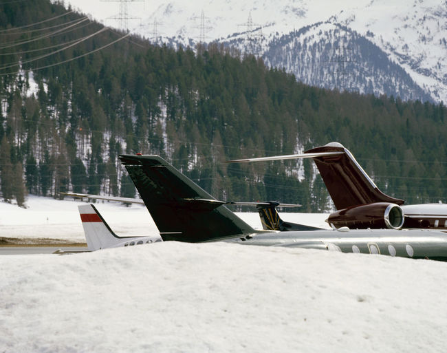 Private jets and planes at the snow covered landscape of airport of St Moritz in Switzerland Christmas Fly Transportation Airplane Airplane Tail Airport Aviation Beauty In Nature Cold Temperature Day Flight Jet Landscape Luxury Mountain Mountain Range Nature No People Outdoors Scenics Sky Snow Travel Destinations Tree Winter