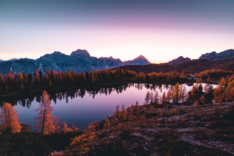 Scenic view of lake by mountains against sky at sunset