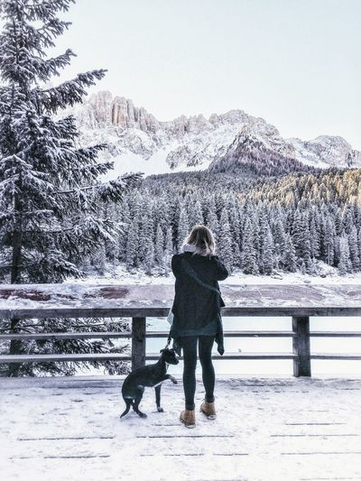 Woman with dog standing on snowy bridge against sky