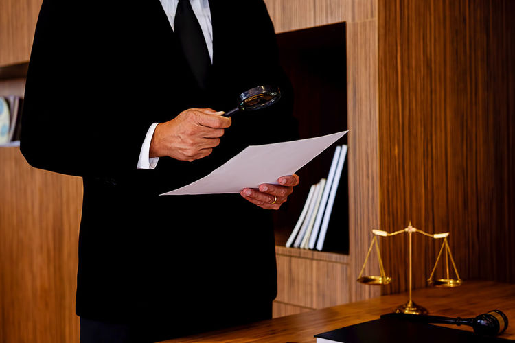 Midsection of male lawyer analyzing document while standing in office