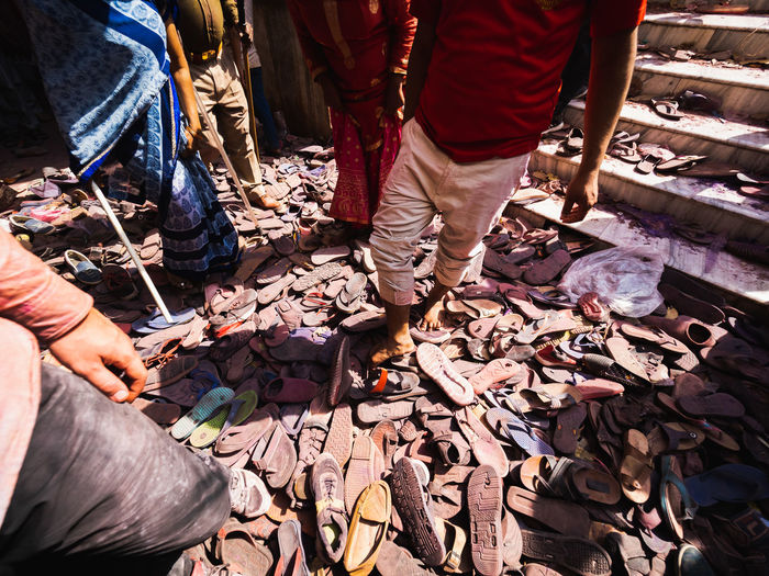 Masses of shoes and footwear are left in piles outside the Banke Bihara Temple prior to the beginning of Phoolon Wali Holi, India. This was the scene 2.5 hours before the doors of the temple even opened. Needless to say I didn't find my shoes at the end of the chaos. Street Photography Photojournalism Shoes Travel Destinations Adventure Holi2019 Olympus Em1x Vrindavan India Banke Bihara Temple Low Section Human Hand Togetherness Men Shadow Human Leg Sunlight High Angle View Human Foot